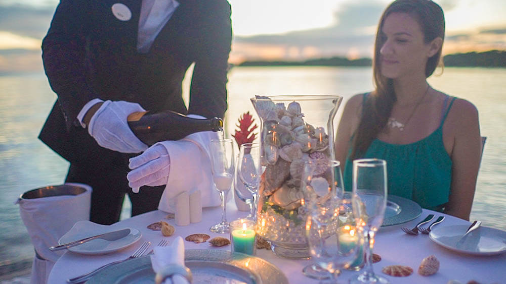 Sandals south coast romantic dinner service on the beach by vacation couple