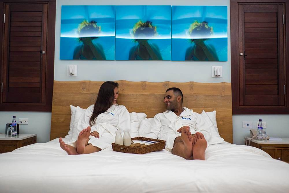vacation couple having a late night butler snack on the bed at sandals sout coast Jamaica room service