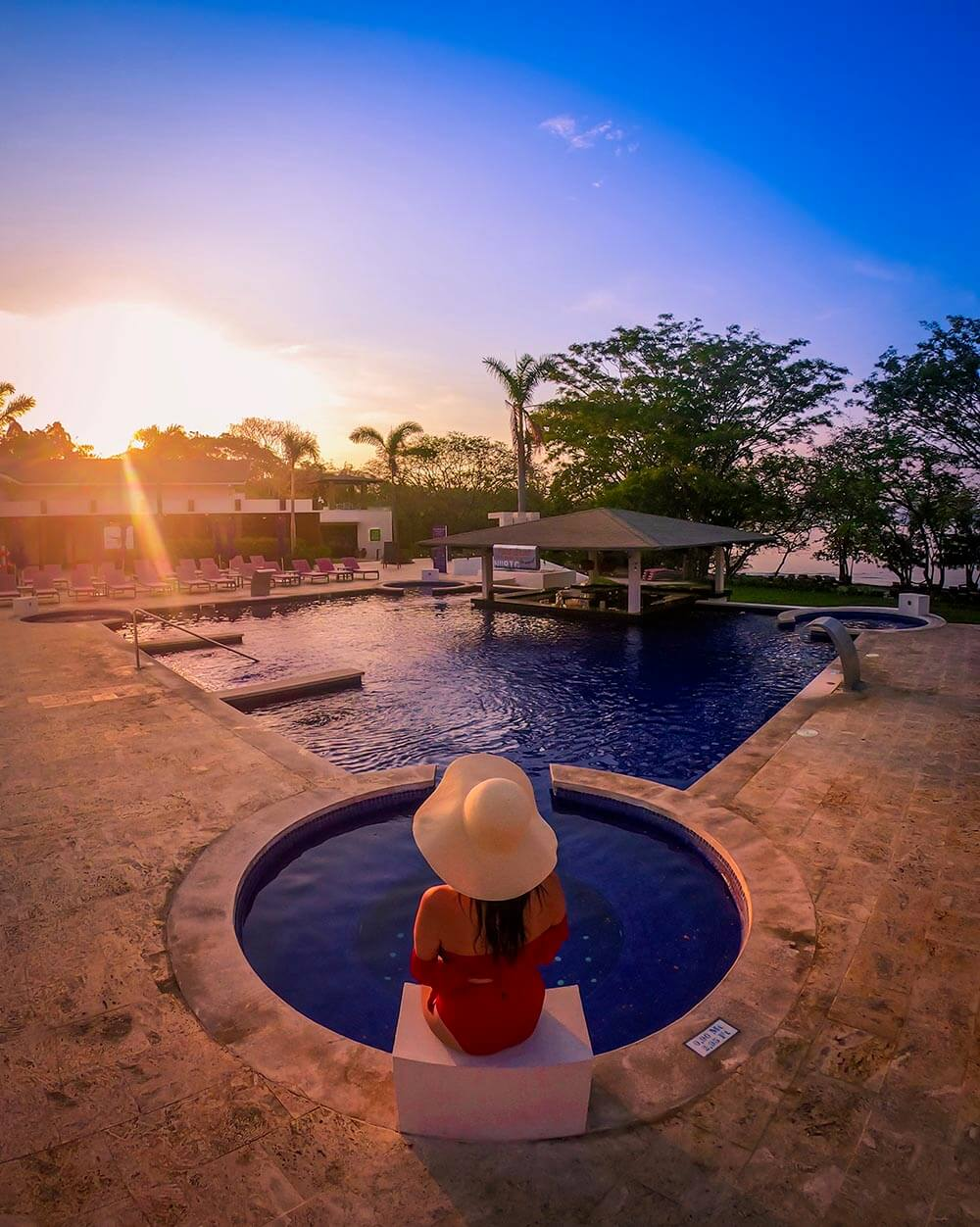 planet hollywood costa rica review girl with hat sitting on side of pool at sunrise