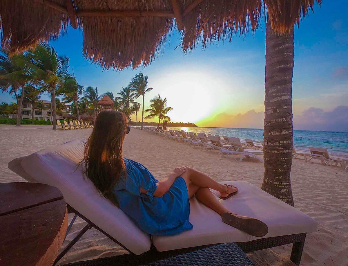 girl sitting on beach chair gazing at sunrise
